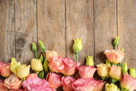 Photo pour Flat lay composition with beautiful Eustoma flowers on wooden table, space for text - image libre de droit
