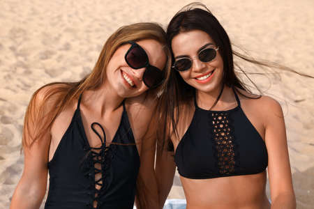 Photo pour Young woman in bikini with girlfriend on beach. Lovely couple - image libre de droit