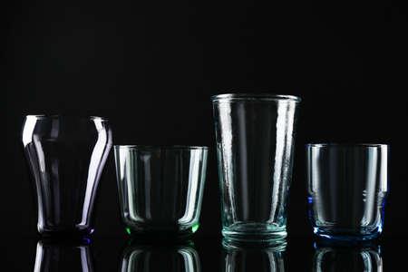 Foto de Set of different colorful empty glasses on black background - Imagen libre de derechos