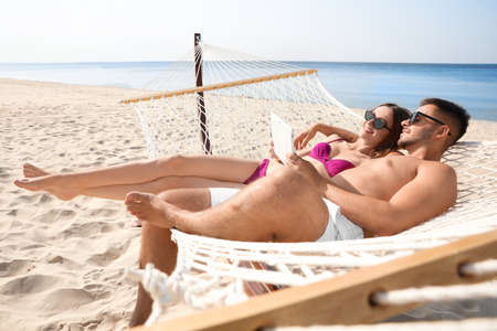 Photo for Young couple with tablet relaxing in hammock on beach - Royalty Free Image