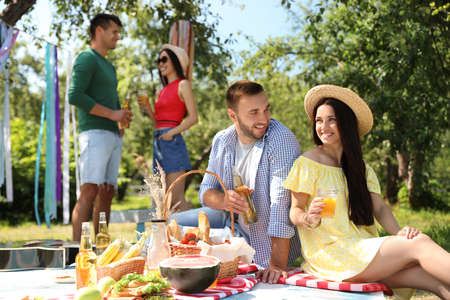 Photo pour Young people enjoying picnic in park on summer day - image libre de droit