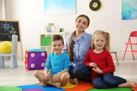 Foto de Kindergarten teacher with children in playroom. Indoor activity - Imagen libre de derechos