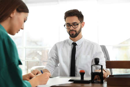 Photo pour Male notary working with client in office - image libre de droit