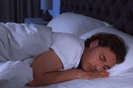 Photo pour Handsome young man sleeping on pillow at night. Bedtime - image libre de droit