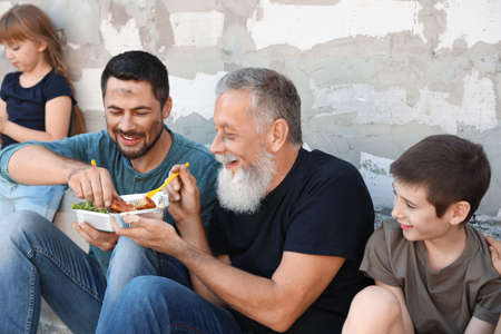 Photo pour Poor people holding plates with food near wall outdoors - image libre de droit