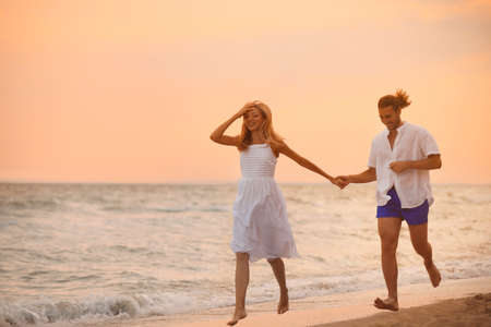 Photo for Young couple having fun on beach at sunset - Royalty Free Image
