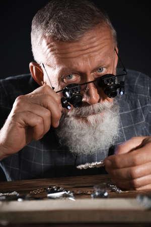 Foto de Male jeweler evaluating diamond brooch in workshop - Imagen libre de derechos