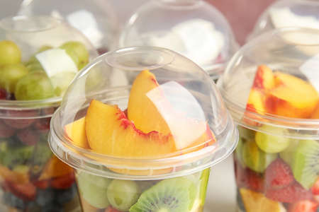 Photo for Fresh tasty fruit salad in plastic cups, closeup - Royalty Free Image