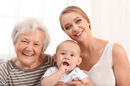 Photo pour Happy young woman with her child and grandmother at home - image libre de droit