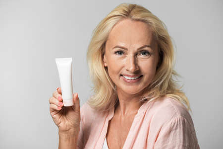 Photo pour Portrait of beautiful mature woman with perfect skin holding tube of cream on grey background - image libre de droit