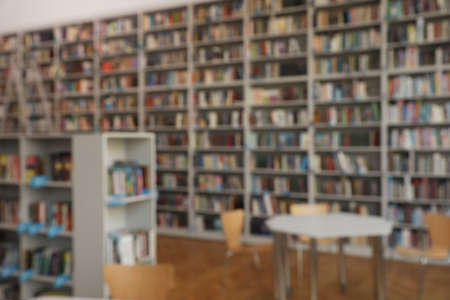 Photo pour Blurred view of bookshelves and table in library - image libre de droit