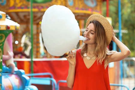 Photo for Happy young woman eating cotton candy in amusement park - Royalty Free Image