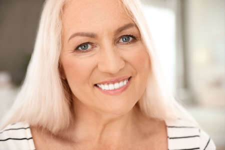 Photo for Portrait of mature woman with beautiful face on blurred background, closeup view - Royalty Free Image