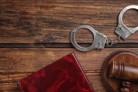 Book, handcuffs and gavel on wooden table, flat lay. Criminal law