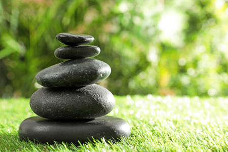 Photo pour Stack of stones on green grass against blurred background, space for text. Zen concept - image libre de droit