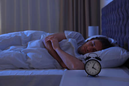 Photo for Alarm clock on nightstand near sleeping young man. Bedtime - Royalty Free Image