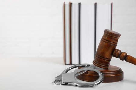 Gavel, handcuffs and books on table against white background, space for text. Criminal law