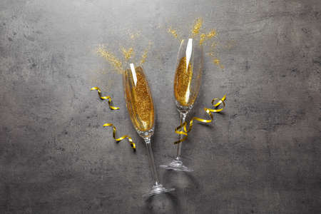 Photo pour Flat lay composition with champagne glasses for celebration on grey stone background - image libre de droit