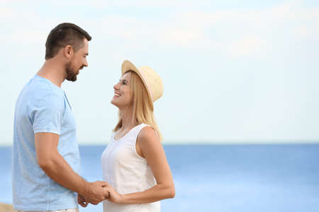 Photo for Happy romantic couple spending time together on beach, space for text - Royalty Free Image