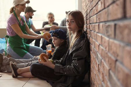 Photo for Teenage girl with other poor people receiving food from volunteers indoors - Royalty Free Image