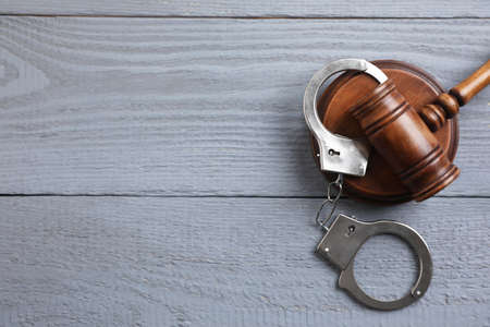Flat lay composition with handcuffs and gavel on grey wooden table, space for text. Criminal law