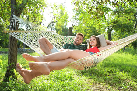 Photo pour Young couple resting in comfortable hammock at green garden - image libre de droit