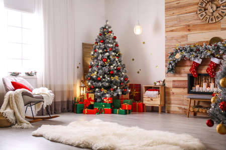 Photo pour Stylish room interior with beautiful Christmas tree and decorative fireplace - image libre de droit