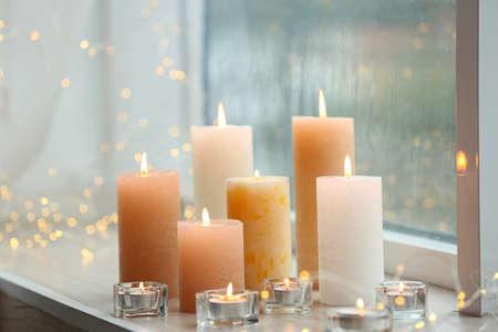 Foto de Beautiful burning candles and fairy lights at windowsill on rainy day - Imagen libre de derechos
