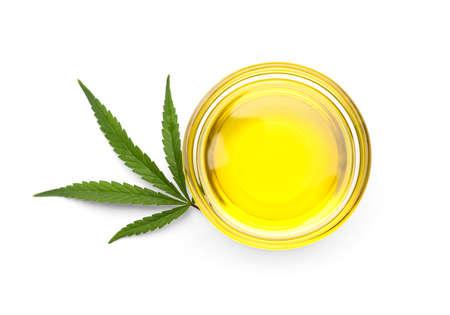 Photo pour Bowl with hemp oil and leaf on white background, top view - image libre de droit