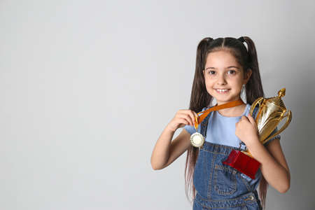 Photo pour Happy girl with golden winning cup and medal on light background. Space for text - image libre de droit