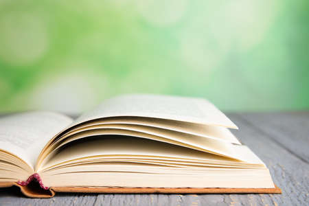 Photo for Open book on grey wooden table against blurred green background, closeup. Space for text - Royalty Free Image
