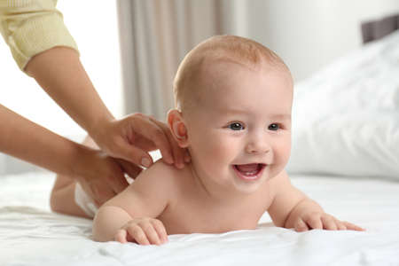 Photo pour Young woman massaging cute little baby on bed indoors - image libre de droit