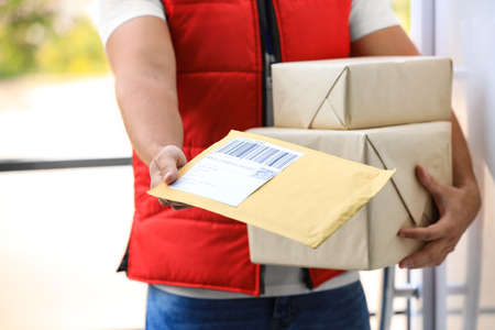 Photo pour Young courier holding parcels on doorstep, closeup. Delivery service - image libre de droit