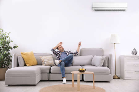 Photo pour Young man switching on air conditioner with remote control at home - image libre de droit