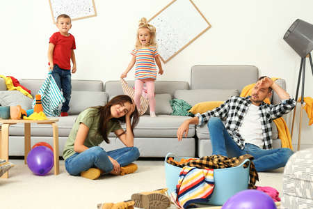 Photo pour Frustrated parents and their mischievous children in messy room - image libre de droit
