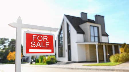 Foto de Red real estate sign near house outdoors on sunny day - Imagen libre de derechos