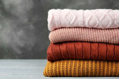 Photo pour Stack of warm clothes on wooden table against grey background. Autumn season - image libre de droit