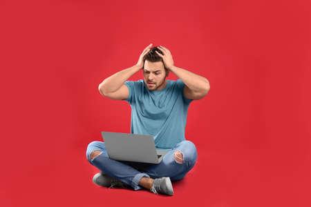 Photo pour Emotional man with laptop on red background - image libre de droit