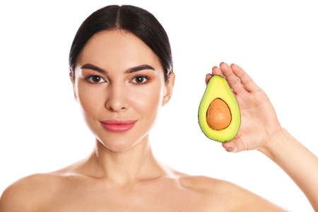 Photo pour Young woman with silky skin after face mask holding avocado on white background - image libre de droit