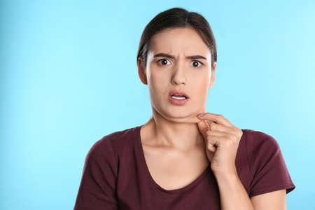 Photo pour Emotional young woman with double chin on blue background - image libre de droit