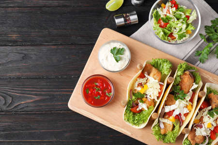 Photo for Delicious fish tacos served on dark wooden table, flat lay - Royalty Free Image