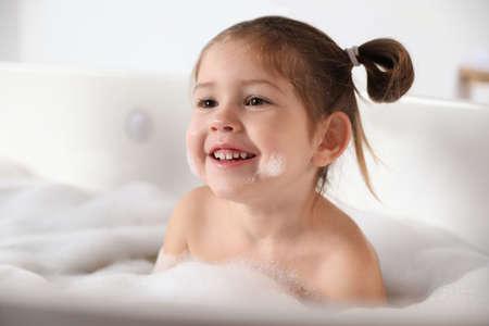 Photo pour Cute little girl taking bubble bath at home - image libre de droit