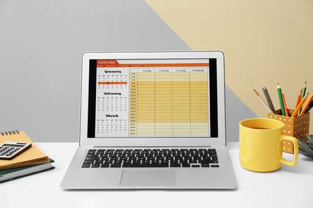 Foto de Modern laptop with calendar on screen in office - Imagen libre de derechos