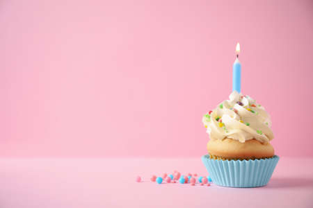 Photo pour Delicious birthday cupcake with candle on pink background. Space for text - image libre de droit
