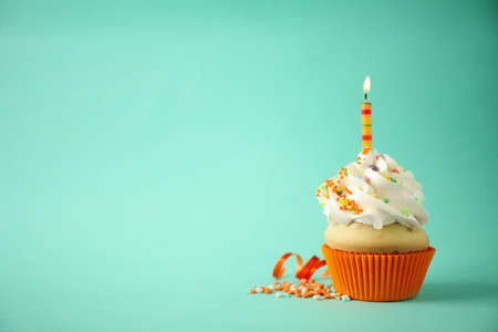 Photo pour Delicious birthday cupcake with candle on light green background. Space for text - image libre de droit