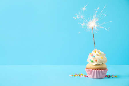 Photo pour Birthday cupcake with sparkler on light blue background. Space for text - image libre de droit