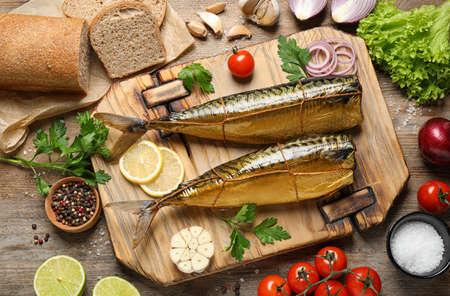 Foto de Flat lay composition with tasty smoked fish on wooden table - Imagen libre de derechos