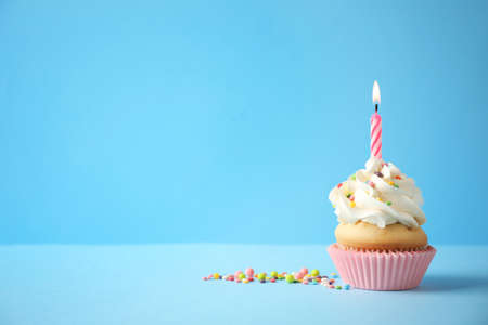 Photo pour Delicious birthday cupcake with candle on light blue background. Space for text - image libre de droit