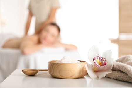 Photo pour Bowl with sea salt and orchid flower on white table in spa salon. Space for text - image libre de droit