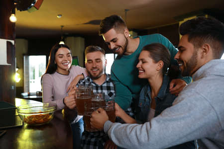 Photo for Group of friends celebrating victory of favorite football team in sport bar - Royalty Free Image